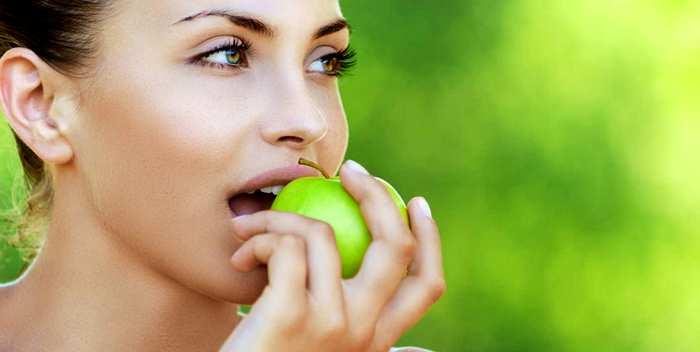 Красивая женщина кушает зеленое яблоко