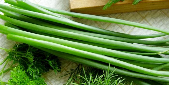 Зеленый лук возле разделочной доски рядом с укропом